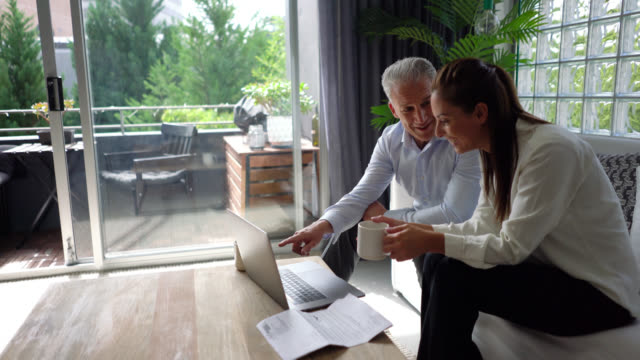 glückliches paar arbeiten von zu hause, an einem projekt mit laptop auf der couch sitzen und lachen - in den fünfzigern stock-videos und b-roll-filmmaterial