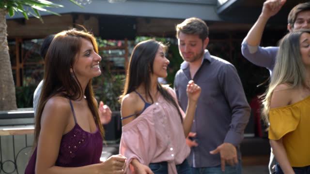 vídeos de stock, filmes e b-roll de casais felizes num bar dançando e cantando, tendo um grande momento - canto