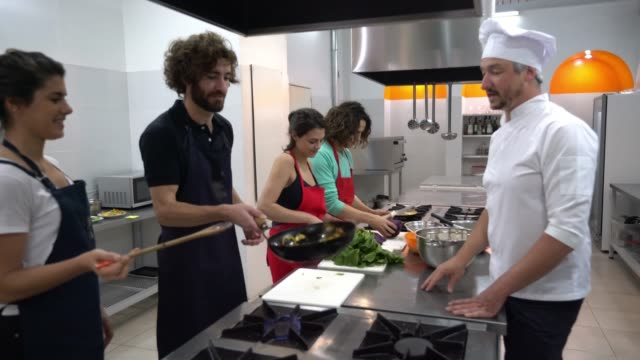 happy couples at a cooking class and head chef teaching them checking what they are doing - learning stock videos & royalty-free footage