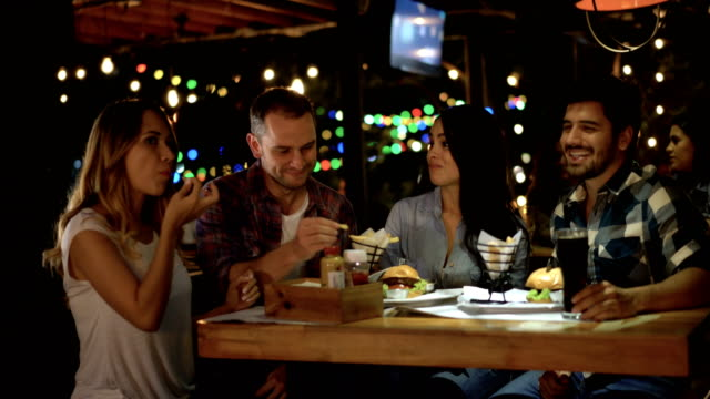 Happy couples at a restaurant enjoying french fries and burgers while talking