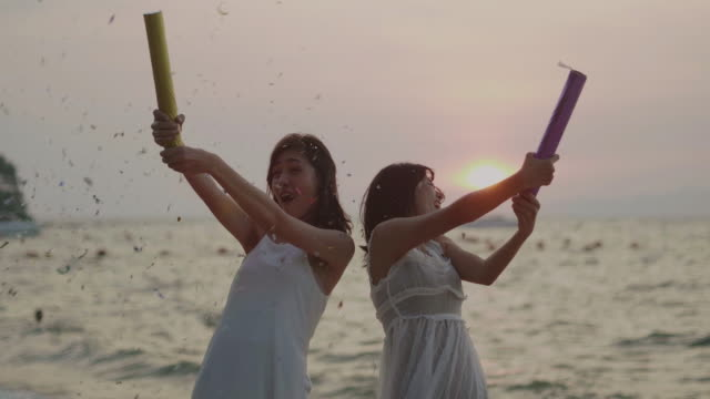 Happy couples woman lighting sparklers and enjoying freedom at beach during sunset.LGBT Vacation.LGBT concep