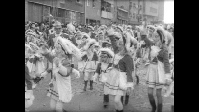 happy crowd sings and dances during the rosenmontag festival in cologne / clowns on parade with cymbals and umbrellas / crowd in similar traditional... - 四旬節点の映像素材/bロール