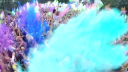 Happy crowd throws paint powder in air, festival atmosphere