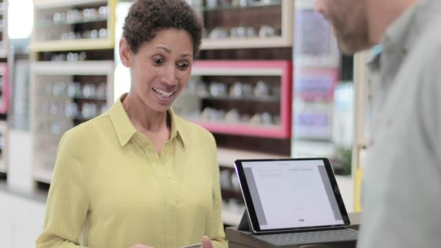 vidéos et rushes de happy customer paying in store - opticien