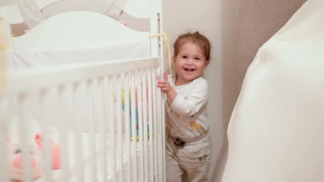 happy cute baby girl playing hide and seek , peekaboo behind a crib in a nursery room - hide and seek stock videos & royalty-free footage