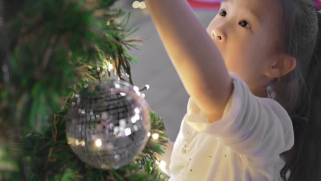 slo mo happy cute little girl decorating christmas tree - cosy stock videos & royalty-free footage