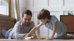 Happy dad helping child son building castle of wooden blocks
