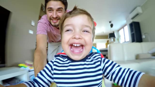 POV Happy dad pushing his son in the walker across the house