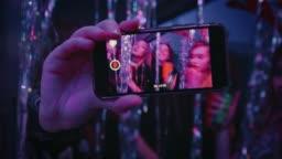 Happy dancing teenagers seen on smart phone screen