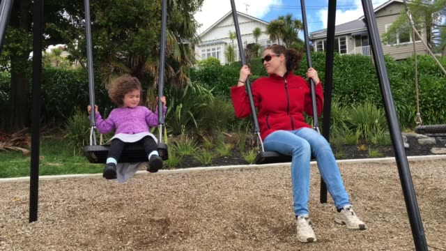 Happy daughter and mother swinging on a swing together