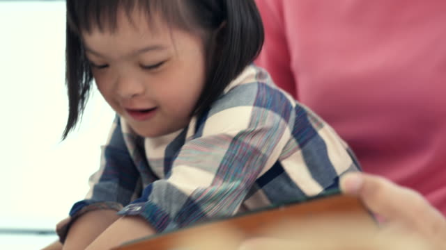 happy disabled girl(2-3 years) using digital tablet with her parent - 2 3 years stock videos & royalty-free footage