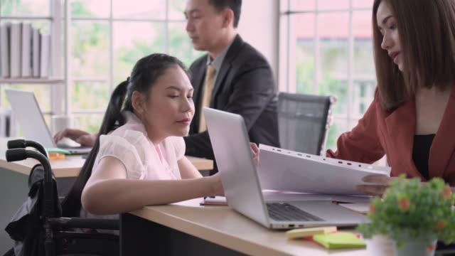 stockvideo's en b-roll-footage met gelukkige gehandicapte vrouw die met zijn twee collega's in bureau werkt - mid volwassen mannen