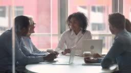 Happy diverse businesswomen handshaking at international negotiations concept