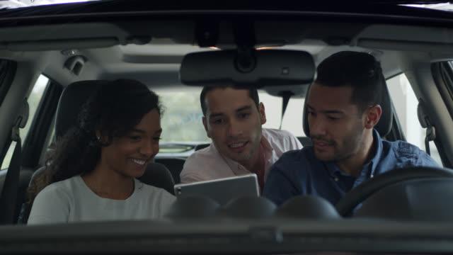 vidéos et rushes de couples heureux divers achetant une voiture au concessionnaire et parlant au vendeur tout en regardant les détails sur une tablette - essai de voiture