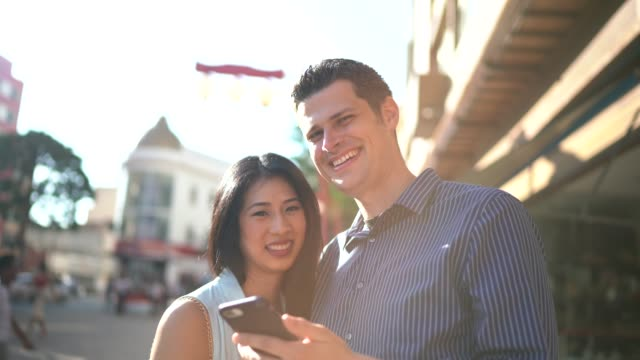 happy diverse couple looking at camera and using phone in the city - liberdade stock videos & royalty-free footage