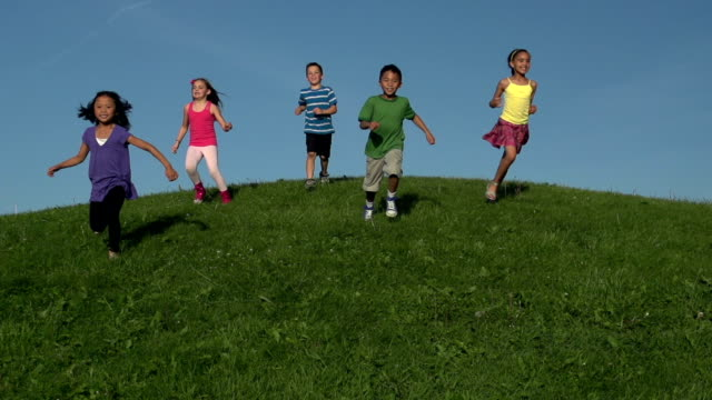 happy diverse kids running down grassy hill in slow motion - hill stock videos & royalty-free footage