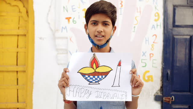 happy diwali deepawali sketch along with a coloured diya lamp wax candle for festival of lights hindu festival drawn by a school boy as he proudly presents it and shows his art work and skills as a face mask hangs around his neck - pencil icon stock videos & royalty-free footage
