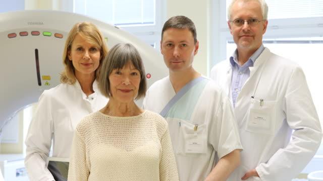 Zufrieden Ärzte und ältere Frau in CAT-Scan-Raum