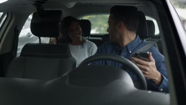 vídeos de stock, filmes e b-roll de motorista feliz de um serviço de solicitação de carro dirigindo uma mulher negra bonita - dirigir