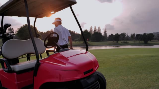 happy driving a golf-cart with clubs golf.sports cinemagraphs - golf cart stock videos & royalty-free footage
