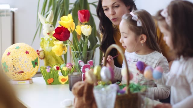 happy easter! a mother and her little daughters coloring easter eggs. stock video - easter stock videos & royalty-free footage