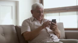 Happy elder senior man holding smartphone using mobile online apps