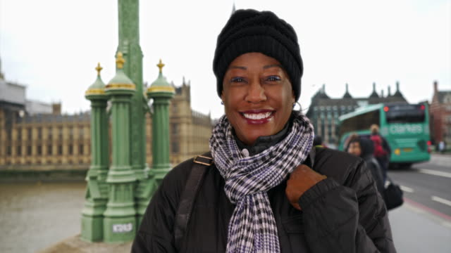 happy elderly black woman tourist stands on westminster bridge smiling at camera - big ben点の映像素材/bロール