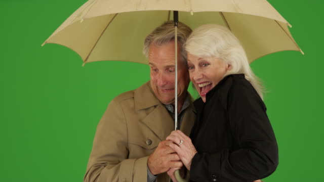 stockvideo's en b-roll-footage met happy elderly couple standing in the rain with an umbrella on green screen - plus key