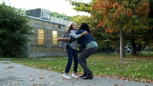 vídeos de stock e filmes b-roll de happy elementary age girl greets mom with hug outside school building - encontro