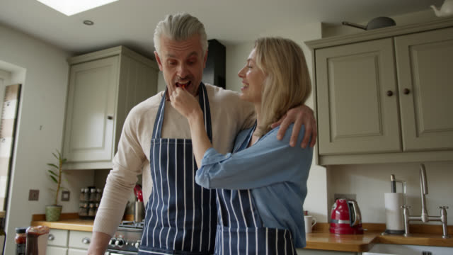 happy english couple cooking together at home and wife feeding husband a bite - mature couple stock videos & royalty-free footage