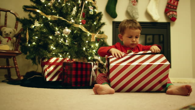 a happy, excited three-year old caucasian boy open a christmas present by the christmas tree on christmas day - unwrapping stock videos & royalty-free footage