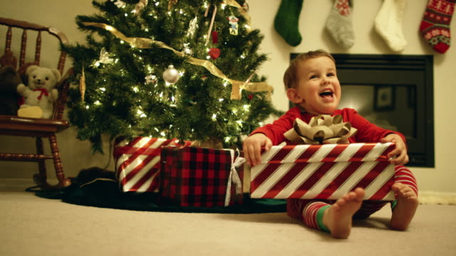 a happy, excited three-year old caucasian boy open a christmas present by the christmas tree on christmas day - stockings stock videos & royalty-free footage