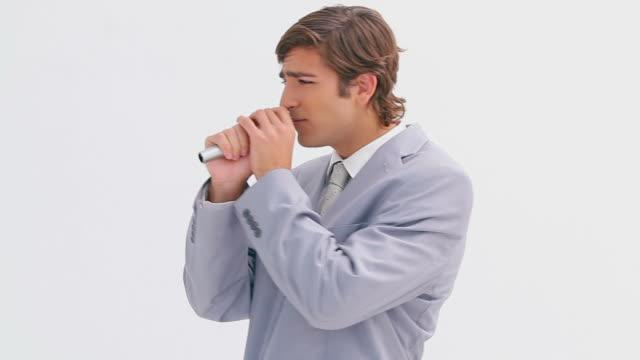 vidéos et rushes de happy executive singing into a cordless microphone - téléphone sans fil