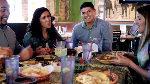 Happy extended Hispanic family having meal together in restaurant