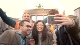 Happy faces of friends unny Friends of different nationalities make selfies in memory of the Brandenburg Gate in Berlin