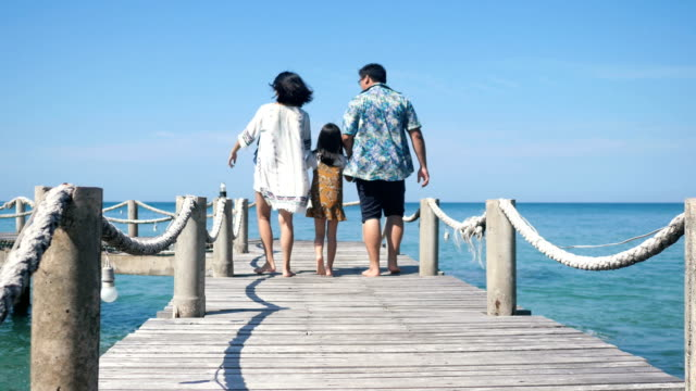 Happy Family Asian walking on a wooden bridge at the pier seaside.4k