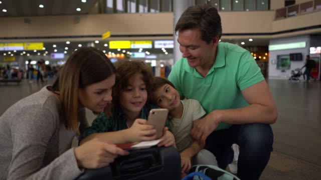 happy family at the airport waiting for their flight and looking at smartphone screen talking - luggage stock videos & royalty-free footage