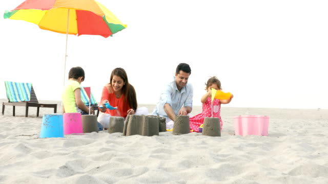 ws happy family building sand castles on beach / india - indian ethnicity stock videos & royalty-free footage
