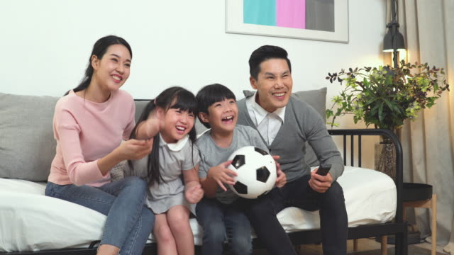 happy family cheering favor football team while watching tv together - east asian ethnicity stock videos & royalty-free footage