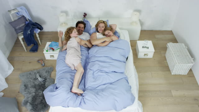 happy family chilling in bed