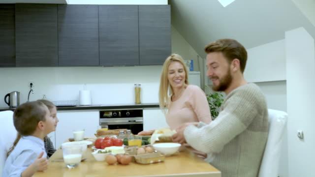 vídeos y material grabado en eventos de stock de familia feliz comunicación teniendo una comida juntos en mesa de comedor. - happy meal