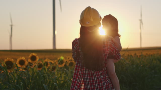 happy family concept, mom engineer and child are playing in sunflowers field at sunset - engineering stock videos & royalty-free footage