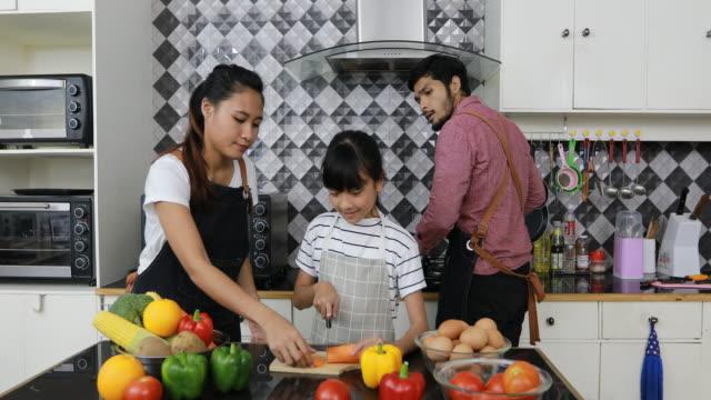 vídeos de stock, filmes e b-roll de família feliz cozinhando na cozinha - povo tailandês