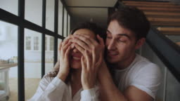 Happy family couple entering home in slow motion. Portrait of hugging couple