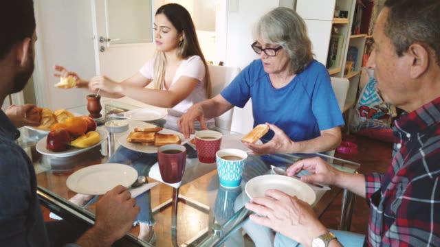 日曜日の朝に自宅で朝食をする幸せな家族 - 甥点の映像素材/bロール