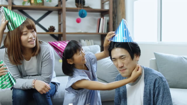 stockvideo's en b-roll-footage met gelukkige familie feest hoeden aantrekken - feestmuts