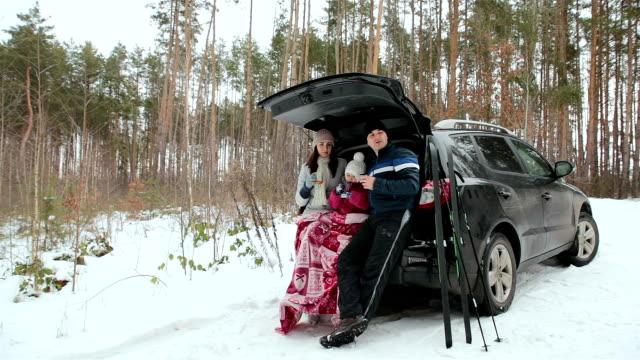 vídeos de stock, filmes e b-roll de família feliz bebe chá e aproveita a paisagem de inverno. - equipamento esportivo