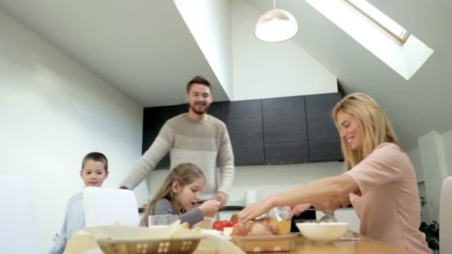 Glückliche Familie Frühstück am Esstisch und miteinander zu reden.