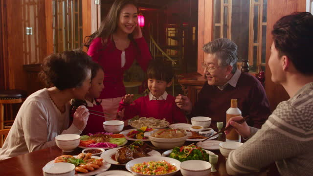 happy family eating dinner for chinese new year,4k - tilt down stock videos & royalty-free footage