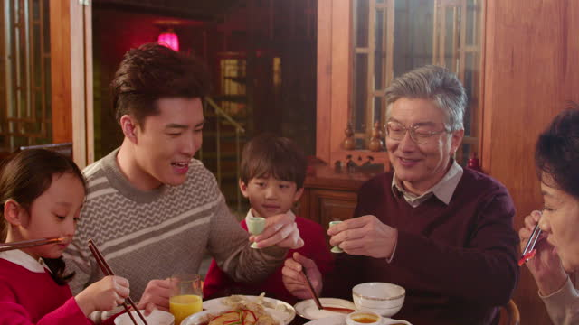 happy family eating dinner for chinese new year,4k - tilt up stock videos & royalty-free footage